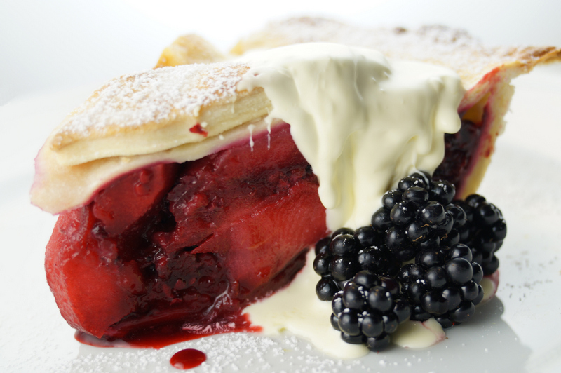 A slice of the pie with cream and berries